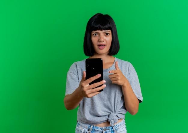 Het verwarde jonge donkerbruine kaukasische meisje houdt en wijst op telefoon