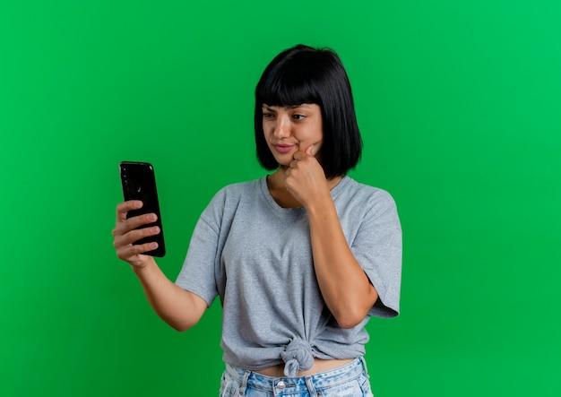 Het verwarde jonge donkerbruine kaukasische meisje zet vuist op kin die telefoon bekijkt die op groene achtergrond met exemplaarruimte wordt geïsoleerd