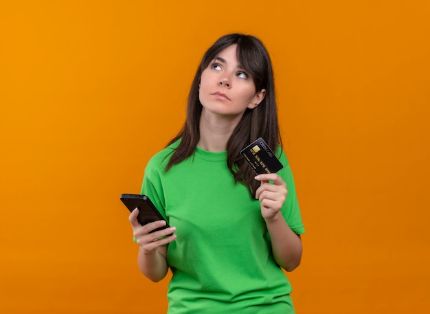 Het verwarde jonge kaukasische meisje in groen overhemd houdt telefoon en houdt creditcard op geïsoleerde oranje achtergrond
