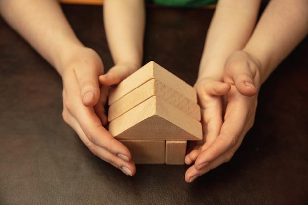 Het verzamelen van een houten constructeur zoals huis. close-up shot van vrouw en kind handen doen verschillende dingen samen. familie, huis, onderwijs, jeugd, liefdadigheidsconcept. moeder en zoon of dochter.