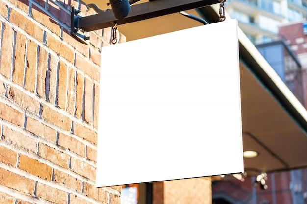 Het vierkante witte concept van het bedrijfsteken op een bakstenen muur