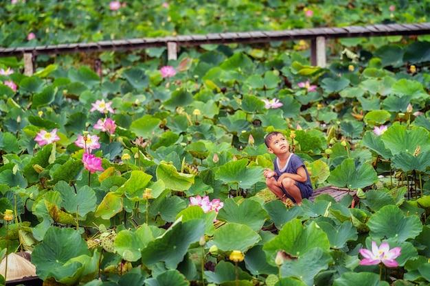 Het vietnamese jongen spelen met de roze lotusbloem over de traditionele houten boot in grote lak
