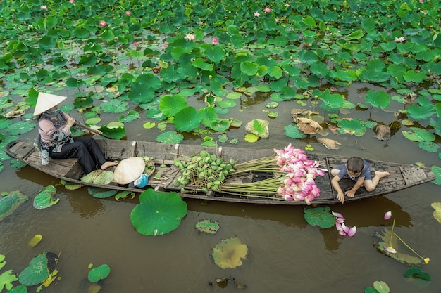Het vietnamese jongen spelen met mammarover de traditionele houten boot