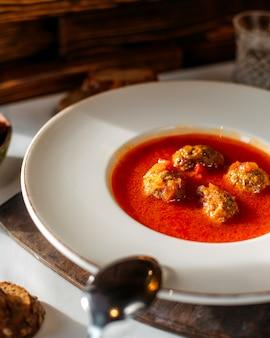 Het vlees van de vooraanzicht tomatoe soep binnen witte plaat op de witte oppervlakte