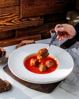 Het vlees van de vooraanzicht tomatoe soep binnen witte plaat op witte backgorund