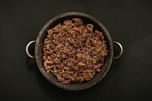 Het vlees wordt gegrild op een stenen plaat. de achtergrond is een zwarte textuur