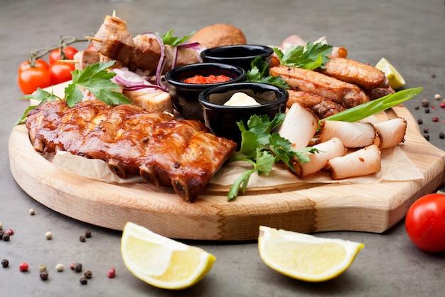 Het vleesbord is gevuld met bezuinigingen en steaks, versierd met kruiden, kerstomaatjes en citroenen. het concept van vlees of bier voorgerecht.