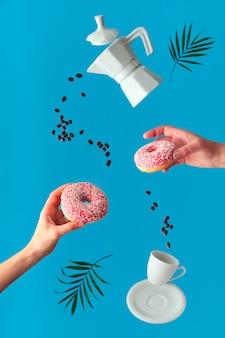 Het vliegende keramische koffiezetapparaat met twee vrouwelijke handen houdt roze donuts. vliegende lijn van koffiebonen.