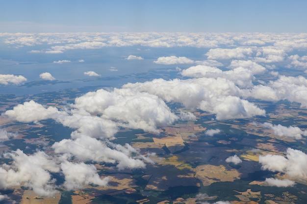 Het vliegtuig dat boven wolken over mooi land hierboven vliegt is de blauwe hemel