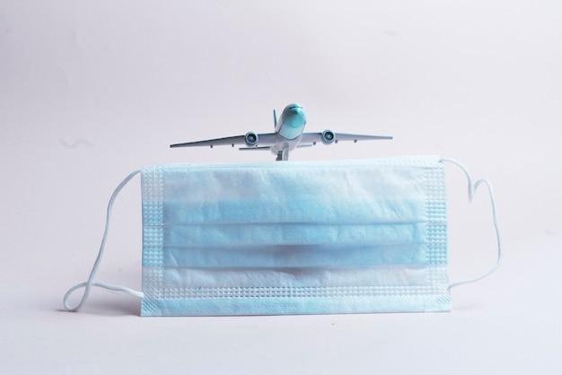 Het vliegtuig en masker als symbool van geannuleerde vlucht tijdens covid-viruspandemie