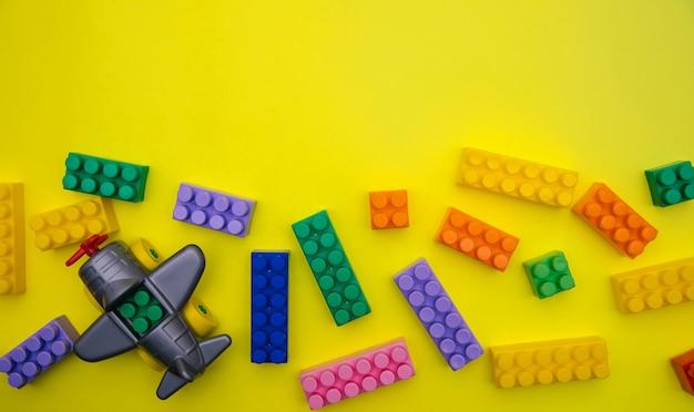 Het vliegtuig is gemaakt van designer onderdelen en blokjes staan verspreid op een gele achtergrond.