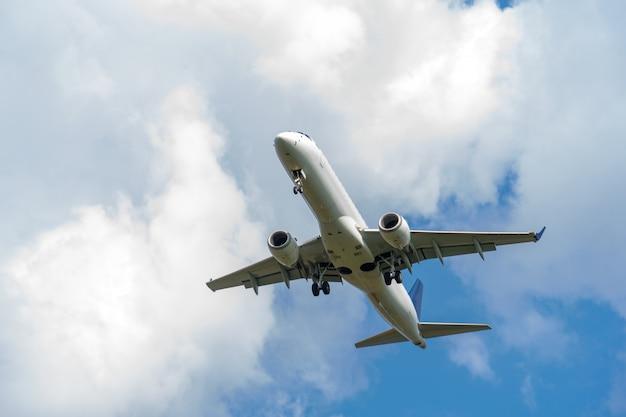 Het vliegtuig landt tegen de hemel met wolken. landingsgestel