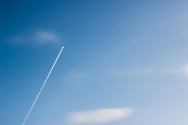 Het vliegtuig vliegt diagonaal in de blauwe lucht tussen de wolken en het zonlicht
