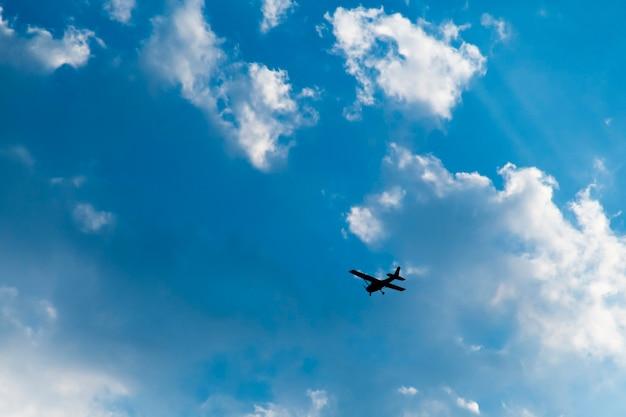 Het vliegtuig vloog in de lucht met witte wolken.