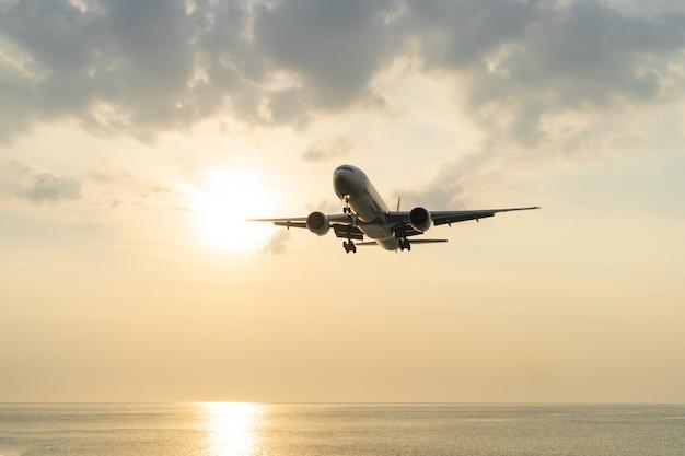 Het vliegtuig zit bij zonsondergang boven de zee.