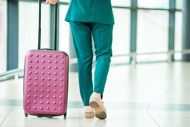 Het vliegtuigpassagier van close-upbenen en roze bagage in een luchthavenzitkamer die voor vluchtvliegtuigen gaan.