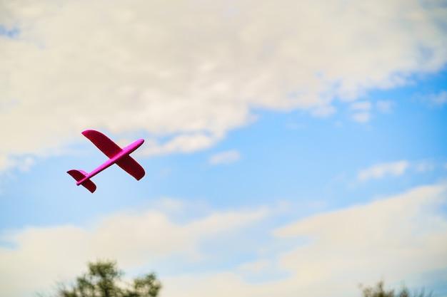 Het vliegtuigstuk speelgoed van roze plastic kinderen dat in blauwe hemel vliegt die met witte wolken wordt omringd