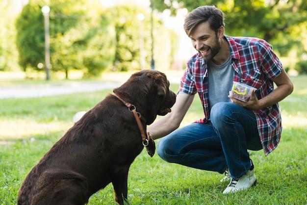 Het voedsel van de mensenholding in container het spelen met hond