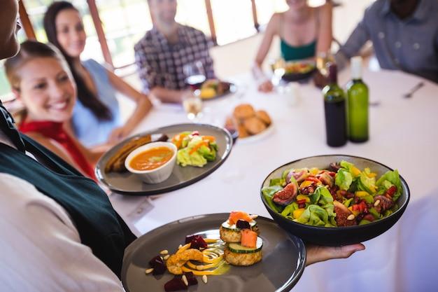 Het voedsel van de serveersterholding op plaat in restaurant
