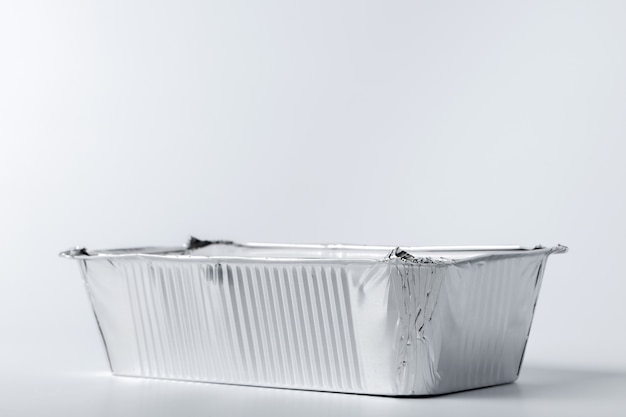 Het voedseldoos van de folie met meeneemmaaltijd op wit