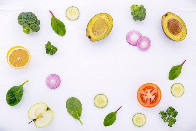 Het voedselpatroon met ruwe ingrediënten van saladevlakte legt op witte houten.