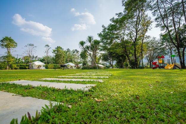 Het voetpad op groene gazons en tent in de tuin