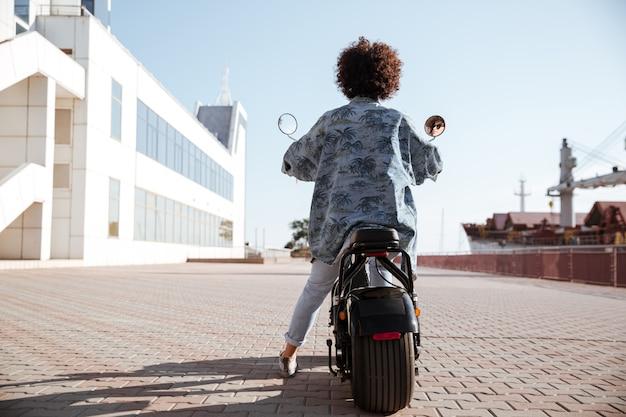 Het volledige beeld van de lengte achtermening van krullende vrouw berijdt in openlucht op moderne motor