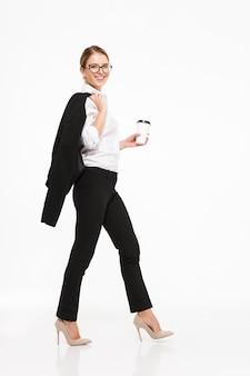 Het volledige beeld van het lengte zijaanzicht van glimlachende blonde bedrijfsvrouw die in oogglazen in studio met kop van koffie en over witte muur lopen