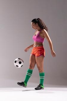 Het volledige geschoten geschikte vrouw spelen met voetbal
