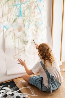 Het volledige geschotene vrouw schilderen op de muur