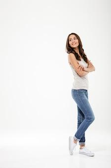 Het volledige lengte tevreden donkerbruine vrouw stellen zijwaarts met gekruiste wapens die terug over grijs kijken