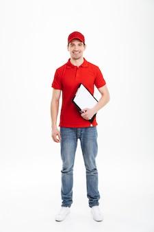 Het volledige lengtebeeld van jonge koeriersmens jaren '20 in rood eenvormig en jeans die op camera kijken en klembord houden, dat over witte ruimte wordt geïsoleerd