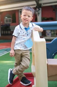 Het volledige lengteportret van glimlachende aziatische 3-4 jaar oude peuterjongen stelt voor camera tijdens het hebben van pret op klimrek bij speelplaats