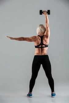 Het volledige portret van de lengte achtermening van een geschikte sportvrouw