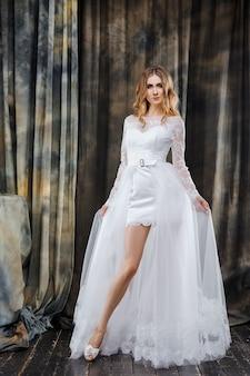 Het volledige portret van de lengtestudio van mooie bruid in korte huwelijkskleding