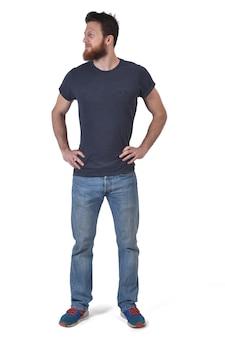 Het volledige portret van een man overhandigt de taille en kijkt naar de zijkant op wit