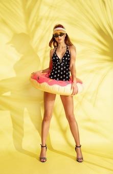 Het volledige portret van het mooie jonge meisje dat op gele studioachtergrond met de palmschaduwen wordt geïsoleerd. vrouw poseren in modieuze romper. gelaatsuitdrukking, zomer, weekendconcept. trendy kleuren.