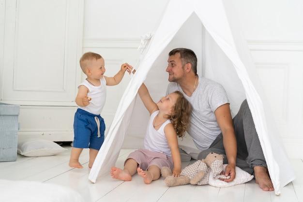 Het volledige schot vader spelen met kinderen met tent