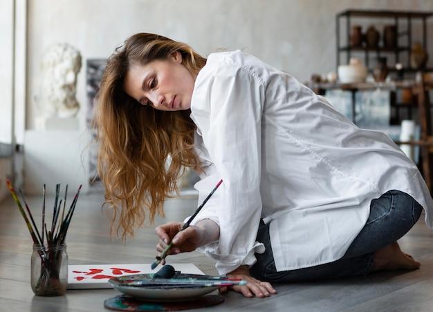 Het volledige schot van de vrouw die op vloer schilderen
