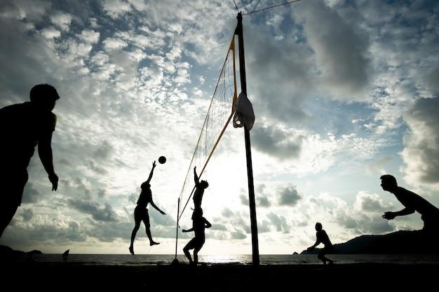 Het volleyballteam van het strand het spelen tijdens zonsondergangtijd
