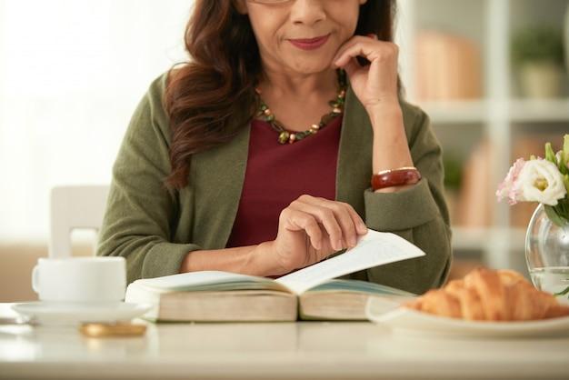 Het volwassen aziatische boek van de vrouwenlezing tijdens ontbijt in ochtend