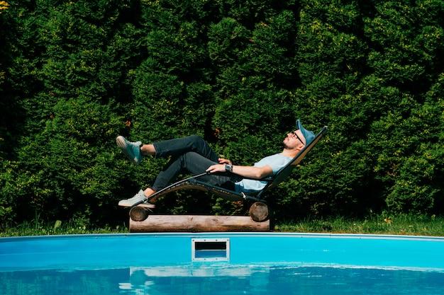 Het volwassen mens ontspannen in chaise-longue voorbij zwembad bij villa in sicilië met muur van groene zuidelijke bomen op achtergrond