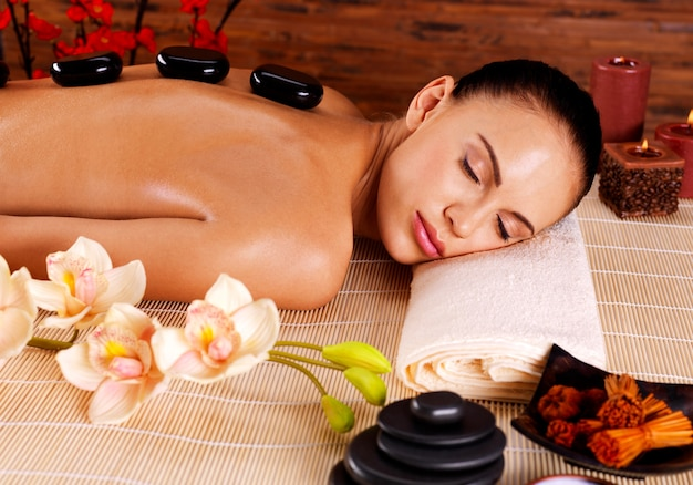 Het volwassen vrouw ontspannen in kuuroordsalon met hete stenen op rug. schoonheidsbehandeling therapie