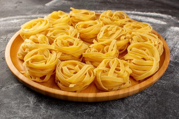 Het vooraanzicht dicht vormde italiaanse deegwaren in bloemvorm ruw en geel op het houten bureau