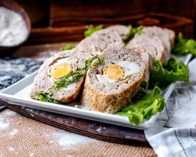 Het vooraanzicht rolt pastei smakelijk lekker met groene salade binnen witte plaat op de bruine oppervlakte