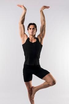 Het vooraanzicht van de atletische mens in bodysuit die een yoga doet stelt