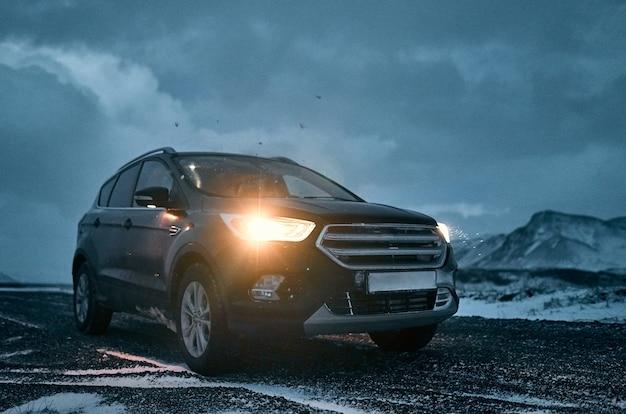 Het vooraanzicht van de auto, koplampen op een lichtjes besneeuwde baan met bewolkte hemel en bergen. aankoop, autoverhuur. reizen, toerisme en vrije tijd.