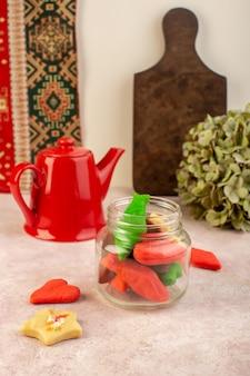 Het vooraanzicht van kleurrijke heerlijke binnen gevormde koekjes kan met rode ketel