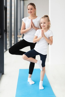 Het vooraanzicht van moeder en dochter het praktizeren yoga stelt thuis