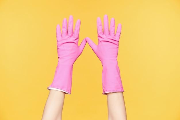 Het vooraanzicht van opgeheven dient rode rubberhandschoenen in die tegen oranje achtergrond worden geïsoleerd, die alle vingers afzonderlijk houden. menselijke handen en lichaam concept